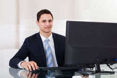 Young Businessman Using Computer At Office Desk Royalty Free Stock Photos