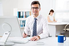 Young businessman using computer in the office. Young handsome businessman smiling at camera when using computer in the office Stock Photography