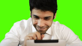 Young businessman using digital tablet on green background stock video footage