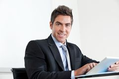 Young Businessman Using Digital Tablet In Office Royalty Free Stock Images