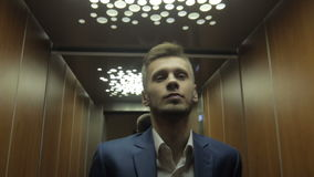 Young businessman using elevator stock video