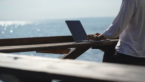 Young businessman using his laptop on the waterfront on sea background. Outdoor cafe stock footage