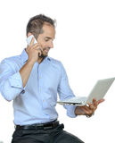 Young businessman using his mobile phone in office. Stock Photos