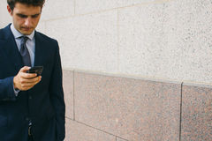 Young businessman using his phone in a street Stock Photos