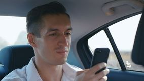 Young Businessman using his Smartphone during Traveling in a Car with a Driver. Man is checking Mails, Chats or the New stock video footage