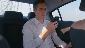 Young Businessman using his Smartphone during Traveling in a Car with a Driver. Man is checking Mails, Chats or the New stock video