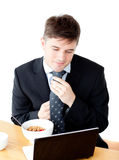 Young businessman using laptop during breakfast Royalty Free Stock Photo