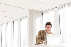 Young businessman using laptop at desk in new office Stock Photography