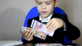 Young businessman using a laptop. Fashion child handsome boy in modern office. sits at a table in an armchair and counts money coi. Ns, euro, pounds and dollars stock video