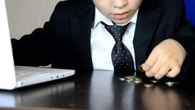 Young businessman using a laptop. Fashion child handsome boy in modern office. sits at a table in an armchair and counts money coi. Ns, euro, pounds and dollars stock footage