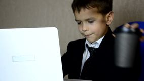 Young businessman using a laptop. Fashion child handsome boy in modern office. sits at a table in an armchair and counts money coi. Ns, euro, pounds and dollars stock video footage