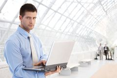 Young businessman using laptop at passage Royalty Free Stock Photo