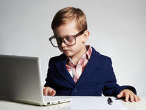Young businessman using a laptop. Serious child in glasses Royalty Free Stock Photography