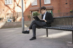 Young businessman using laptop while sitting on bench Royalty Free Stock Photos
