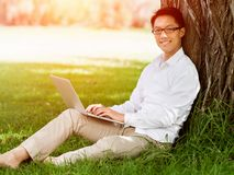 Young businessman using laptop while sitting outdoors Royalty Free Stock Photo