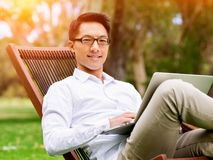 Young businessman using laptop while sitting outdoors Stock Images