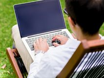 Young businessman using laptop while sitting outdoors Royalty Free Stock Photos