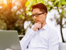 Young businessman using laptop while sitting outdoors Stock Photos