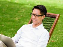 Young businessman using laptop while sitting outdoors Stock Photography