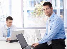 Young businessman using laptop smiling in office stock photo
