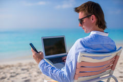 Young businessman using laptop on tropical beach Stock Image