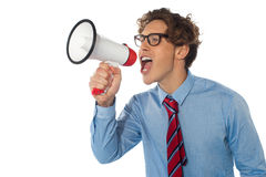 Young businessman using megaphone. Isolated over white background Royalty Free Stock Photography