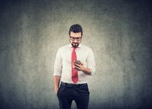 Young businessman using a mobile phone. Young handsome business man using a mobile phone and smiling royalty free stock photo