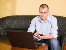 Young businessman using mobile phone and laptop. Royalty Free Stock Photography