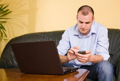 Young businessman using mobile phone and laptop. Royalty Free Stock Photo
