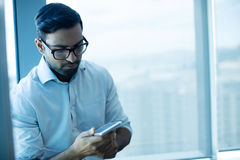 Young businessman using mobile phone. At office Royalty Free Stock Photo