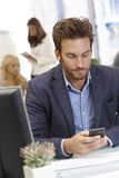 Young businessman using mobilephone at desk Royalty Free Stock Photography