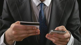 Young businessman using online banking credit card on a smart phone stock footage