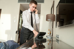 Young businessman using phone in hotel room Royalty Free Stock Image