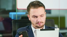 Young man using a phone and a tablet in the office. A young businessman using a smartphone and a tablet in the office. Close-up. Dolly shot. Soft focus stock footage