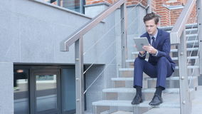 Young Businessman Using Tablet, Browsing, Sitting on Stairs Outside Office. Creative designer , businessman stock video