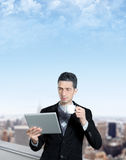 Young Businessman Using A Tablet Computer. Young businessman with a cup of coffee uses a digital tablet on the roof of business center. Blurred cityscape with Stock Photos