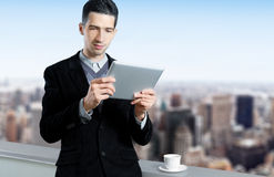 Young Businessman Using A Tablet Computer. Young businessman with a cup of coffee uses a digital tablet on the roof of business center. Blurred cityscape with Stock Images