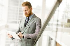 Young businessman using tablet and looking at his watch Royalty Free Stock Photo