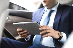 Young businessman using tablet pc while sitting on back seat of a car. Caucasian male business executive by a taxi and looking at royalty free stock photo