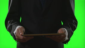Young businessman using a tablet pc in a virtual business environment on green screen stock video footage