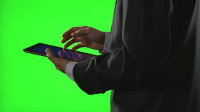 Young businessman using a tablet pc in a virtual business environment on green screen. 4k stock video