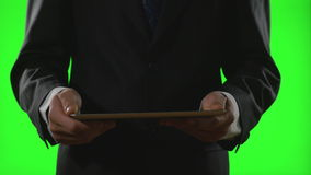 Young businessman using a tablet pc in a virtual business environment on green screen stock video