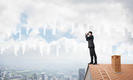 Businessman standing on roof and looking in binoculars. Mixed media Royalty Free Stock Photos