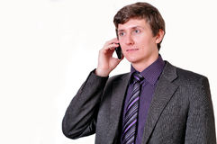 Young businessman in violet tie speaks by phone. On white background Stock Images