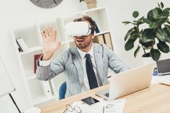 Young businessman in vr headset with laptop sitting. In office Royalty Free Stock Image