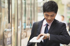 Young businessman waiting for the bus and checking his watch at the bus stop in Beijing, China Stock Image