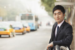 Young businessman waiting at the bus stop for the bus Stock Images