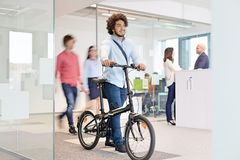 Young businessman walking with bicycle while colleagues in background at office Stock Image