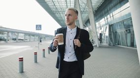Young businessman walking near office building and drinking coffee. Handsome guy enjoy morning coffee to go slow motion stock footage
