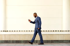 Young businessman walking outdoors and using cell phone Stock Photography